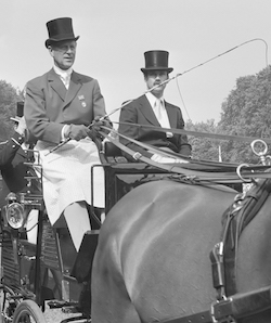 A black and white photograph of Prince Phillip and a male companion on horseback; Phillip is holding a horse-whip