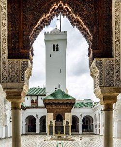 A view through an archway into the courtyard of the Qayrawiyyin mosque in Fes, Morocco. There is a tiled marble floor and a fountain in the middle, with a portico at the rear and a Moroccan type square minaret behind it.