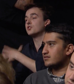 A young white man wearing an open-collared black shirt, with hands moving as he talks, sitting in a TV studio audience. A South Asian man is sitting in front of him.