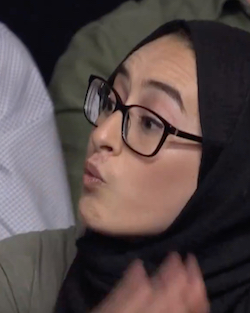 A young South Asian woman wearing a black headscarf and black glasses, sitting in a TV studio audience.