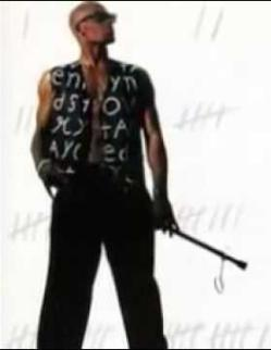 Picture of R Kelly, a Black man with a shaven head wearing a black shirt (open to reveal his chest) with handwritten letters on it in white, black trousers, and holiding a stick in his hand with a cycle mirror near the end.