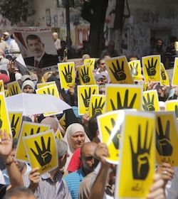 A group of demonstrators in Egypt holding up yellow signs showing hands with four fingers raised, a reference to the Rabaa Massacre of 14th August 2013. Another demonstrator is holding a picture of president Morsi.