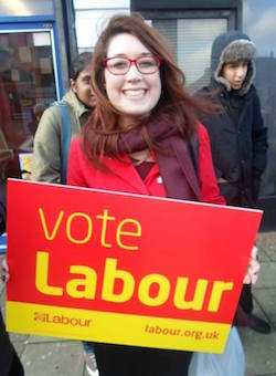 "Picture of Rhea Wolfson, a young white woman with below shoulder length brown hair, wearing red glasses and a bright red jacket, holding a sign saying ""Vote Labour"". Two South Asian men are walking behind her."