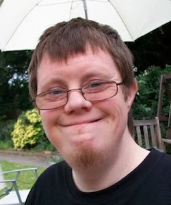 Picture of Richard Handley, a young white man with Down's syndrome. He has a short beard and is wearing glasses with thin black rims and standing underneath a free-standing umbrella in a garden; a wooden and a metal chair can be seen behind him.