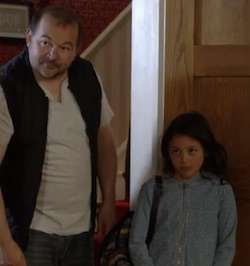 Roya (right), a young, mixed-race white/Asian girl, wearing a light blue top wtih a white pattern on it, holding a large bag over her shoulder, with her unnamed male foster carer (left), a well-built white man with a moustache, wearing a white T-shirt, a black quilted waistcoat, and an old pair of jeans.