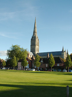 A picture of an English cathedral with a tall spire, with a large two-storey red-brick house in front, across a large lawn.