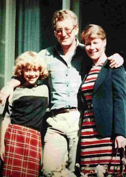 Picture of a girl, a man and a woman (all white) standing in front of a window. The girl (Sam) has curly hair and is wearing a black top with a white or light grey stripe across the upper chest and a red and white tartan knee-length skirt. The man (Russell) has a light-coloured shirt with no tie, and a beige pair of trousers. The woman (Carole) has short blonde hair and is wearing a white, red and black striped dress and a black jacket and is holding a bag in her left hand. The man's arms are round both the other two.
