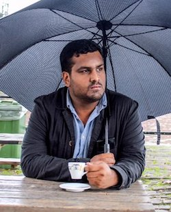 A picture of a youngish South Asian man with a short beard and moustache wearing a blue shirt with no tie and a dark jacket over it, sitting at an outdoor table under a black umbrella holding a small cup of an identifiable drink in his hand, with a saucer underneath it.