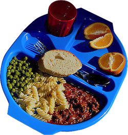 A school dinner, consisting of a blue tray with compartments containing pasta, peas and mincemeat, an orange cut into quarters, a red cup of water, a piece of French bread and a fork and spoon