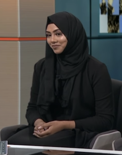 Selina Begum, a young South Asian woman with braces on her teeth wearing a black headscarf and abaya-type dress.