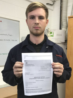 Picture of Shane Ridge, a young white man with short blond hair and a slight beard wearing a dark blue boiler suit standing in a room with white painted breeze-block walls with a whiteboard behind him, holding a letter in his hands headed 'Immigration Enforcement'