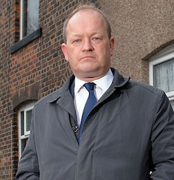 A picture of Simon Danczuk, a middle-aged, balding white man wearing a white shirt, dark blue tie and grey jacket with his lips turned down, standing in front of some old brick houses