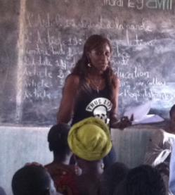 "Picture of Sister Fa, a black woman with long braided hair, wearing a sleeveless black T-shirt with ""Thug Life"" and a skull on it, standing in front of a blackboard with French writing on it, with an audience in the foreground"