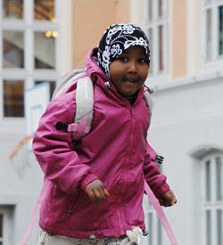 A young girl of Somali appearance wearing a pink jacket and black and white flower patterned headscarf, running.