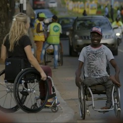 Sophie Morgan, a young white woman in a wheelchair, facing Adamson, a young black man in a wheelchair with one of his legs bent over the other.