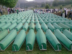Image of rows of coffins each with a green covering, with groups of people, mainly women, on each side and some among the coffins, in a valley