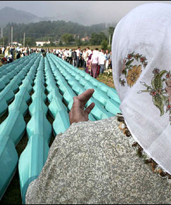 Picture of woman looking at coffins of men massacred at Srebrenica