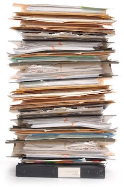 A stack of papers, including a ring binder at the bottom