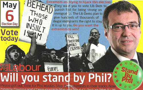 A6 card with a picture of Phil Woolas next to a black & white image of Muslim demonstrators with slogans like 'Behead those who insult Islam', with Woolas's own slogans 'Stand by Phil' and 'Please get out. Vote for Phil Woolas. Stop the extremists in their tracks. Now.'