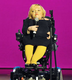 Picture of Stella Young, a white woman of short stature in her 30s in a powered wheelchair, wearing a black dress that comes down to just below her knees, holding a microphone, against a purple background