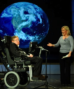 Picture of Stephen Hawking, an elderly white man in a wheelchair, with his daughter Lucy Hawking, a white woman wearing a grey tight-fitting top and black trousers, with a picture of the earth on a black background behind him.