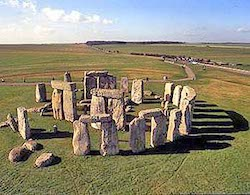 A picture of Stonehenge, a collection of standing stones, some with stone lintels on top, on a plain with a path leading behind it to a car park.