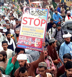 "A photograph of a rally in Pakistan, showing South Asian men in a variety of headwear including turbans, holding aloft a sign that reads ""Stop blasphemers at social media, blasphemous sketches contest in Holland""."