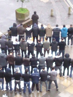 Five rows of young Muslim men standing in the open facing in the same direction, praying, with another man (the imam) in front of them.