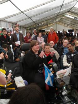 A marquee with a mostly seated audience facing the camera. Susan Archibald, a white woman wearing a black jumper and trousers in an electric mobility scooter, is speaking.