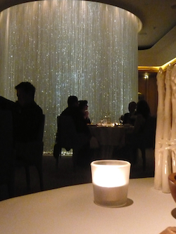 A picture of four people sitting around a table at the Dorchester hotel, with a large circle of hanging lights dangling from the ceiling behind them. The people are silhouetted. There is a small candle in the foreground.