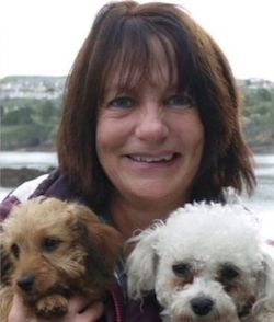 Picture of Teresa Colvin, a middle-aged white woman with shoulder-length brown hair, holding two small dogs in her hands. Behind her is a river estuary with trees and buildings on the other side.