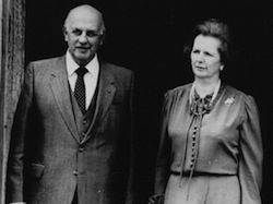 Black & white picture of PW Botha (a bald white man) wearing a grey suit and tie with a white shirt on left, with Margaret Thatcher, wearing a dress with two bows at the neckline and buttons down the front.