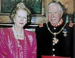 Colour picture of Thatcher wearing a pink velvet-appearance dress, with Augusto Pinochet, an old man wearing a black jacket with gold buttons, with various military medals and decorations