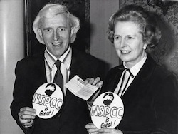 "Picture of Margaret Thatcher, on right wearing a black jacket, with Jimmy Savile, a white man with almost shoulder-length hair wearing a jacket and tie, both holding ""NSPCC is great"" (NSPCC = National Society for the Prevention of Cruelty to Children)"