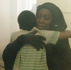 Shakira, a black woman wearing a black gown and veil which is flipped back over her head, embraces Isaac, a young boy in a green-and-white striped T-shirt who is facing away from the camera. Dust is visible as it follows a bombing.
