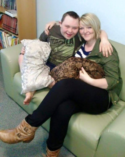 A picture of Thomas Rawnsley, a young man with Down's syndrome wearing a green/khaki T-shirt, sitting on a sofa next to Becky, a young woman with blonde hair wearing a blue and white striped T-shirt, a green jacket, black leggings and brown leather boots.