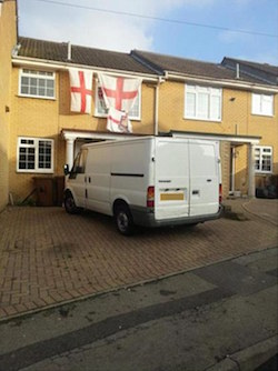 An image of a small yellow-brick house with three St George's Cross flags hanging from the roof, one obscuring an upstairs window, with a red brick driveway and no front garden, with a white Ford Transit van parked outside it.