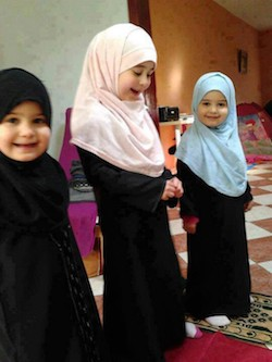 A picture of three young girls in long black dresses and headscarves, one in black, one in light pink and another in light blue. One of them is standing on a prayer mat.