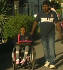 Picture of Thusha Kamaleswaran, a 7-year-old South Asian girl, being pushed in a wheelchair (to school) by her father, a South Asian man in his 30s.