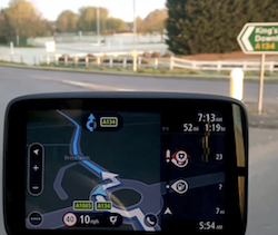 A TomTom Go Professional series truck sat-nav showing a roundabout on the A134 road in England; a sign pointing to King's Lynn and Downham Market can be seen behind it in the windscreen.