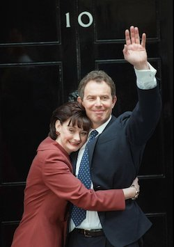 Picture of Tony Blair, a clean-shaven white man in his 40s with matted dark hair, wearing a dark grey suit with a blue tie with small yellow deocrations, waving to crowds from a doorstep with the number 10 on the door, with his wife Cherie, a white woman of similar age wearing a red jacket with shoulder-length brown hair, embracing him.