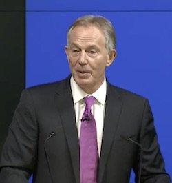 Picture of Tony Blair wearing a dark suit with a pinkish/purple tie with a microphone attached, standing in front of a blue background
