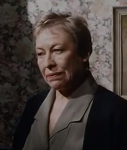 A screen grab of a white woman in her 50s standing against a backdrop of a flowery papered wall, talking to a man who is off to the left
