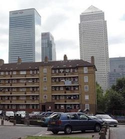 A stock picture of a six-storey red-brick block of flats, with grey skyscrapers in the background, one of them bearing an HSBC logo. In the foreground is the car park for the block of flats.
