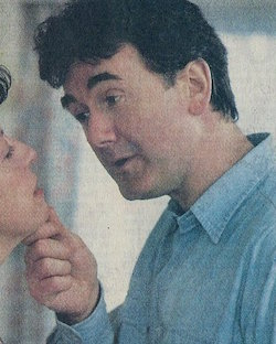 A still from a TV soap, showing a white man with dark hair wearing a blue shirt holding a woman's face (mostly off camera) up by the chin, talking at her with a clearly threatening look on his face.