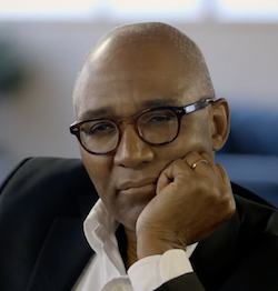 Picture of Trevor Phillips, a middle-aged Black man thick-rimmed, black wearing glasses, with his hand pressed up to his face.
