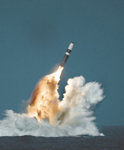A missile being launched from the sea, with fire projecting from its rear and much water thrown up in the air
