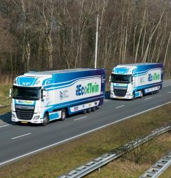 "Two articulated lorries with DAF XF tractor units bearing Dutch number plates, painted in a blue and white striped livery with ""EcoTwin"" and ""European Truck Platooning"" logos on both"