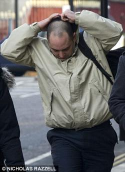Picture of Richard Trunkfield, a white man wearing a hoodie trying to hide his face from photographers as he approaches court.