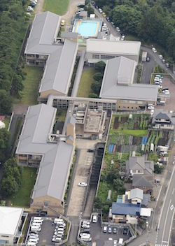 An aerial shot of a group of buildings, including two large Z-shaped and one smaller L-shaped building, plus a small outdoor swimming pool, some gardens and a car park and surrounding roads.